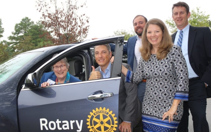 5 Rotary members standing in front of Rotary Vehicle